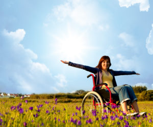 Image of woman in an open field using a wheelchair.